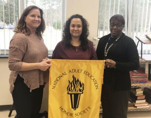 Student with instructors and NAEHS flag.