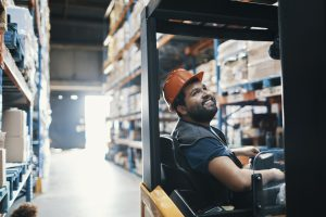 Close up of a person forklift driver working in a warehouse.