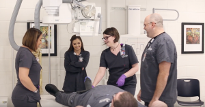 An instructor and four students working in a radiography class.