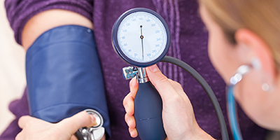 Close-up of person taking a patient's blood pressure.