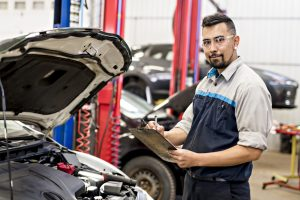 Mechanic job in uniform working on car