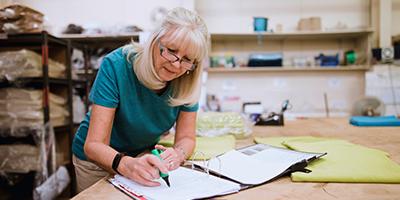 Businesswoman is doing paperwork in her stock factory.