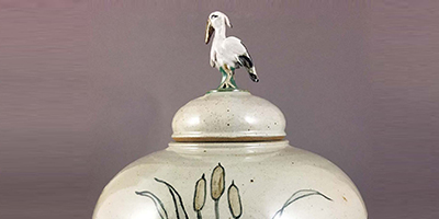 Jugtown Crane jar on a gray background.