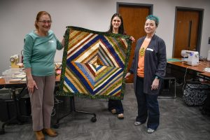 Three students hold up their quilt in a classroom.