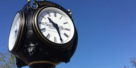 SCC clock with blue sky in background.