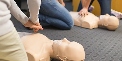 A group of adult education students practicing CPR chest compression on a mannequin.