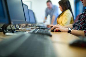 Close of up hands at a computer keyboard.