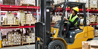 Person driving forklift in a warehouse.