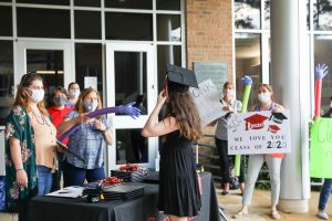 With staff celebrating in the background with signs outside Van Dusen Hall, a student receives her diploma cover during the drive-through HSE graduation celebration at the Pinehurst campus.