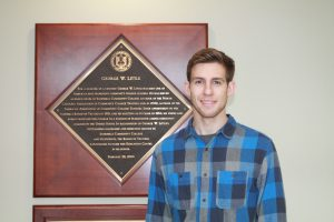 Matthew Pittman poses for a photo in front of a plaque.
