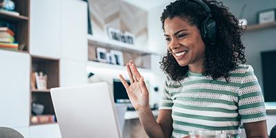 Student waving at a laptop wearing headphones.