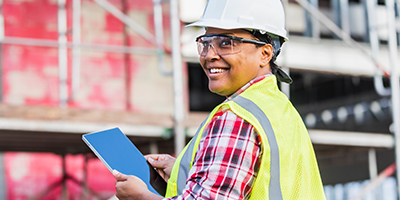 Person smiling, at a construction site, holding an iPad.