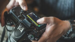 Close up of a DSLR camera in someone's hands.