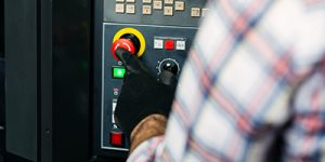 Close up of person pushing a red button on a machine.