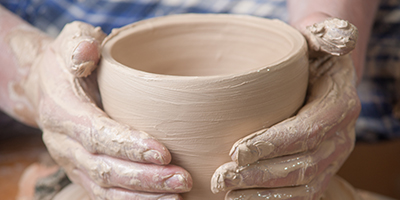Hands of a potter, creating an earthen jar on the circle.