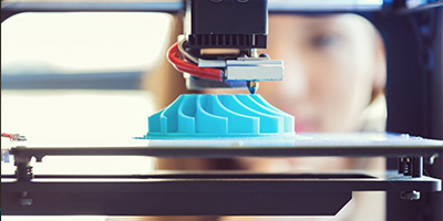 Close up of a 3D printing machine, making a blue object.
