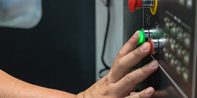 Student pushes a green button on a piece of machinery.