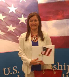 Isabel Cain poses in front of a photo of an American flag, smiling, on the day she earned her U.S Citizenship.