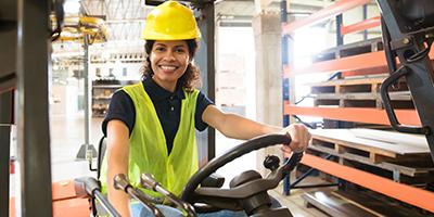 Smiling worker sitting on forklift.