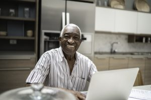 Student smiling in their kitchen, in front of a laptop.
