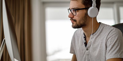 Person working on computer, wearing headphones.