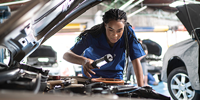 Woman repairing a car in auto repair shop.