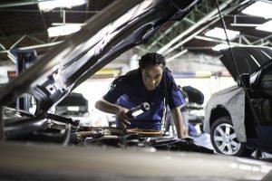 Person repairing a car in auto repair shop.