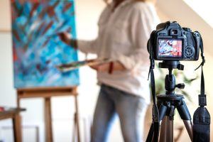 Artist painting, DSLR camera in foreground.