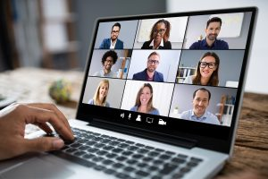 Close up of a laptop screen with different people on it during a video conference.