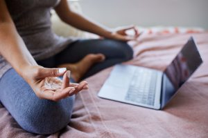 Close up of person meditating with an open laptop.
