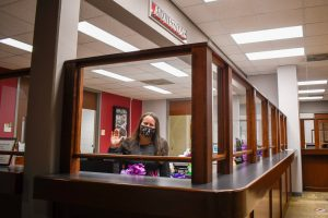 Staff member waves from behind a barrier in Student Services.