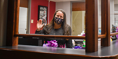 Staff waves to camera behind a barrier in Student Services.