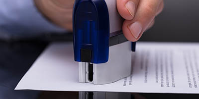 Close up of a hand stamping a document.