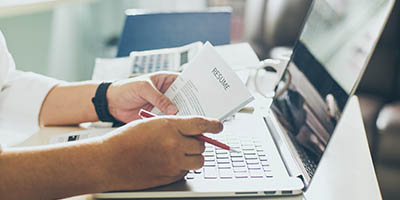 Close up of hands holding a resume, with laptop underneath.