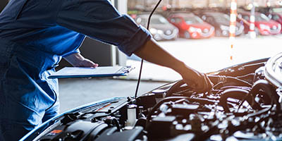Close up of a person working under the hood of a car.