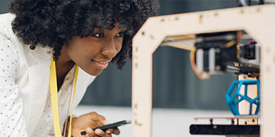 Person looking at a 3D printer, with an object being printed.