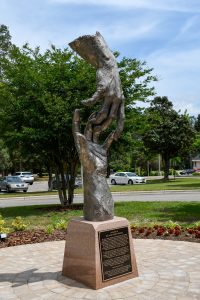 Statue dedicated to Dr. Thomas on the Hoke Center campus. A hand reaching down to lift another up, made of bronze with a silver nitrate patina finish.