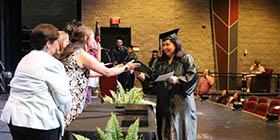 Graduate receives their HSE diploma in Owens Auditorium.