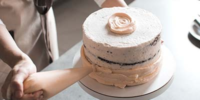 Close up of a person piping icing on to a cake.