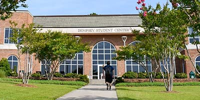 Wide angle of Dempsey Student Center, student walking on walkway.