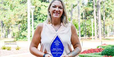 Megan Ramsey, smiling, holding her award outside on the SCC campus.
