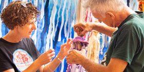 Two people installing an art exhibit.