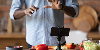 Person recording on a smartphone, produce in background.