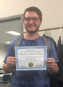 Thad Cagle proudly displays his recently earned High School Equivalency (HSE) diploma earned through the Sandhills Community College HSE in the Community program.
